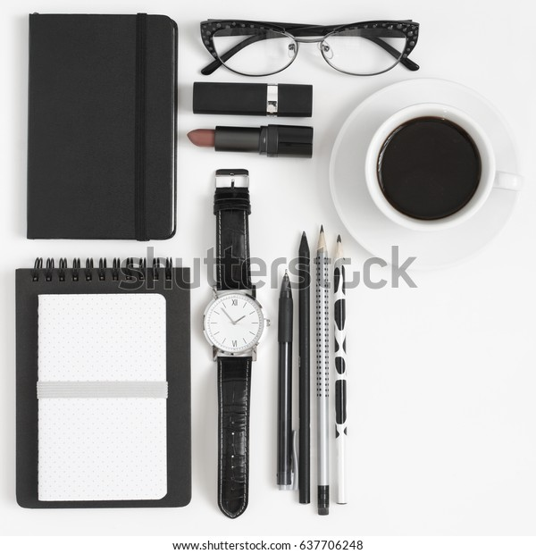 Black and white still life: notepads, pen, pencils, glasses, watch, cup of coffee and lipstick. Business lady accessories. Top view, flat lay.