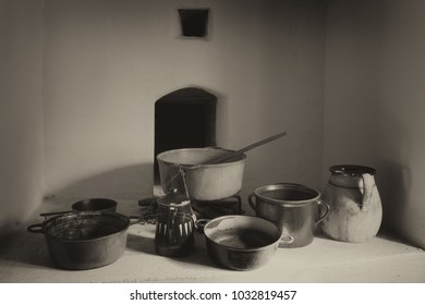 Black and white still life of old pots and kitchen utensils.