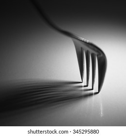 Black and white still life photography of a fork and its shadow on white table under natural light