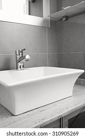 Black and white still life view of a new sink with silver tap in a stylish bathroom in quality design home, interior. Bath room and washing facilities in hotel room, travel and aspirational lifestyle.