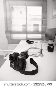 Black and white still life working from home desk with professional photographic equipment, camera, computer monitor, electronics indoors. Media college student technology, hobbies recreation leisure.