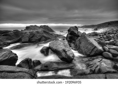 A black and white stormy seascape with big rocks and moving sea water. Dark rain clouds hanging in the sky.