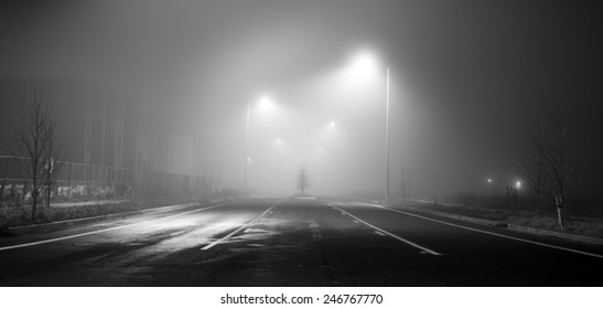 Black and white street at night with heavy fog