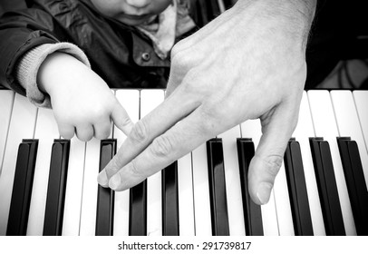 Black and white street photography of a piano player with a young pupil.