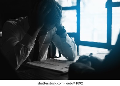 black and white Stressed businessman with head in hands