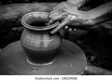 Black and white striking image of a potter's hands shaping soft clay to make an earthen pot