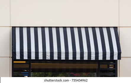 black and white striped awning over glass window with light yellow concrete wall as background.