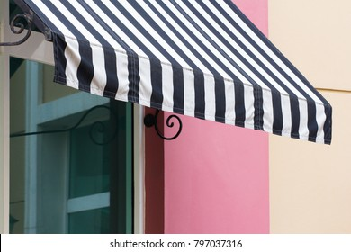 black and white striped awning over glass window of restaurant