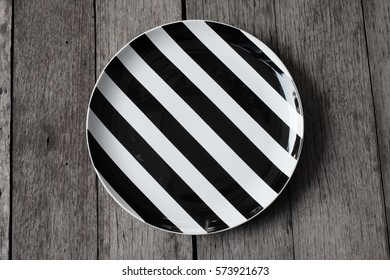 Black and White striped plate on the wooden table background for montage food product display on top view