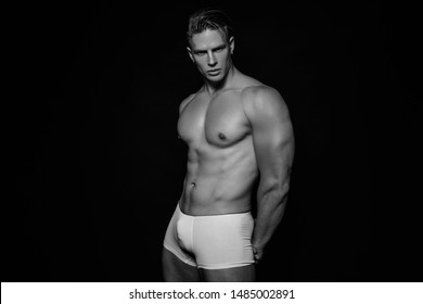 Black and White Strong stripped muscle male model in white underwear on black isolated font background