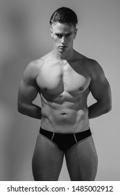 Black and White Strong stripped muscle male model in black underwear on white isolated font background