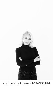 Black and white studio portrait of an attractive blond woman in a black turtleneck jumper against plain background