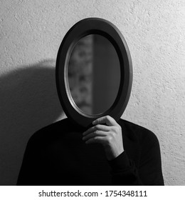 Black and white studio portrait of young man holding oval mirror on face. Background of textured wall.