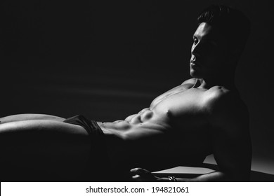 black and white studio shoot of strong athletic man on grey background