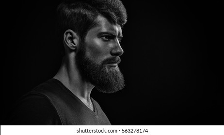 Black and white studio shot of confidence attractive hipster Dramatic light concept Black background Copy space Bearded man