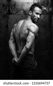 black and white studio shot of strong athletic man on dark grunge background