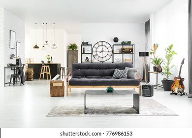 Black and white stylish man cave interior with industrial table, couch and home bar in the background