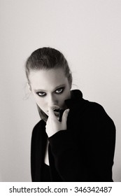 Black and white stylish portrait of a girl hides her face behind the black jacket