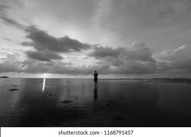 Black and white sunset scenery of  lonely man standing over the beach.