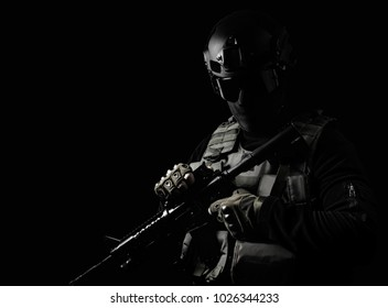 Black and white swat soldier posing. Black and white photo of equipped swat soldier standing with rifle on black background.