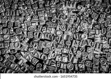 A black and white textured background of lead type-setting letter blocks with various fonts, upper- and lowercase, antique letters.