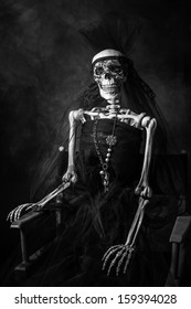 A black and white three quarter shot of a skeleton in a black wedding dress sitting in a directors chair with a necklace and a black veil.