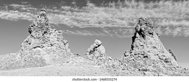 Black and white, three spires on top of barren rocky hilltop, a short spire in between two tall Pinnacles.