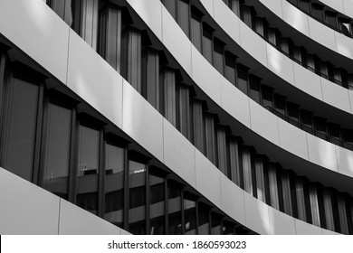 Black and white tone, close-up and detail of exterior curvature facade with contrast colour material of black windows and white aluminium panels in wavy shape.