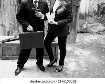 Black and white tone, a man and a woman wearing suit and tie standing and holding money and gun. Shooting photography Illegal money laundering drug trade, dark business concept.