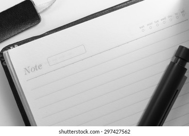 black and white tone for  sad emotion , paper with line and date inside of notebook and pen