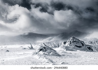 Black and white toned snapshot of highest mountains in winter during snow storm.