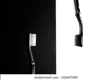 Black and white toothbrushes on a black and white background. Flat lay, top view, copy space. Black and white image.