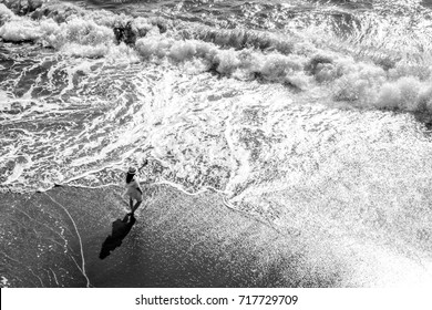 Black and white top view photo of a girl in white dress and white hat admiring and photographing the waves of the ocean. Captured on the Californian coast.