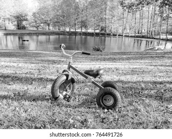 black and white trike cycle outdoors with water background