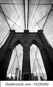 Black and white upward image of Brooklyn Bridge in New York