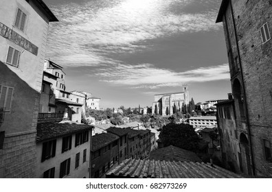 Black and white urban vista of traditional homes in Siena, Italy with Basilica san Domenico in the background