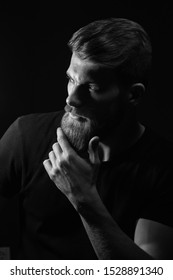 Black and white vertical image of attractive pensive young man looks into the distance stroking his beard over black background