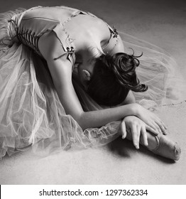 Black and white view of beautiful ballet dancer bending on floor with tutu and point shoes stretching back, conceptual emotional expression, flexibility, stage indoors. Artistic female performer.