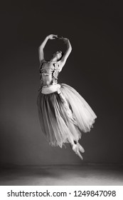 Black and white view of classical ballet dancer jumping up effortlessly on stage, indoors. Concept energy, power strength, lightness and harmony. Female beauty movement discipline training.