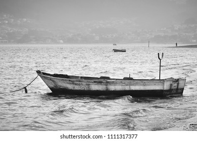 Black and white view of arustic fishing boat moored on seashore on a cloudy and stormy day. It represents loneliness.