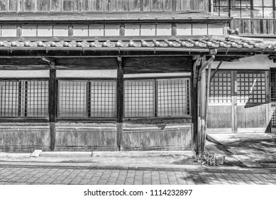 Black and white view of the front facade of an old delapitated traditional Japanese wooden house with sliding window screens.