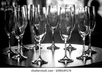A black and white view of a group of champagne glasses arranged on a table.