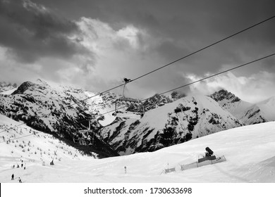Black and white view on chair-lift, snowy ski track prepared by snowcat, skiers in ski resort. High winter mountains, cloudy dark sky. Ski area Mottolino, Italian Alps. Livigno Lombardy, Italy Europe