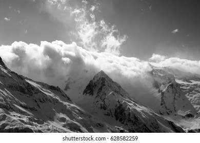 Black and white view on snow sunlight mountains in clouds. Caucasus Mountains, region Dombay.