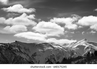 Black and white view on sunlight snow mountains and sky with clouds. Caucasus Mountains. Svaneti region of Georgia.