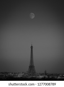 Black and white view of Paris, France, city skyline with a full moon rising and aligned with the famous and romantic Eiffel Tower and its many buildings.
