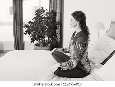 Black and white view of woman sitting on bed doing yoga during morning, home bedroom interior. Healthy female meditating, mind training, wellness mindful sport, indoors. Recreation lifestyle.