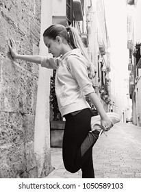 Black and white view of young woman exercising in city street, stretching leg muscles, sport outdoors. Fitness working out healthy training. Teenager female healthy leisure recreation lifestyle.