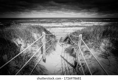A black and white vignette photo of a rope-lined path through large sand dunes to a wide, empty ocean beach and white rolling waves.