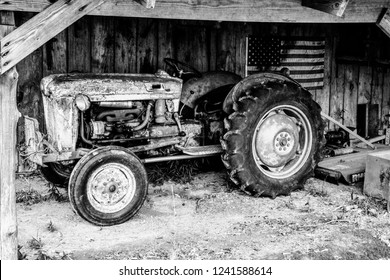 Black and white of a vintage or antique tractor in an dimly lit barn